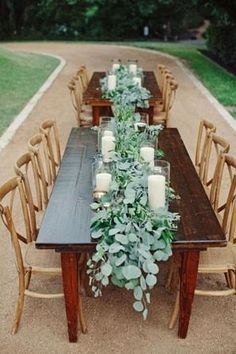 eucalyptus leaves and large candles down center of long reception tables