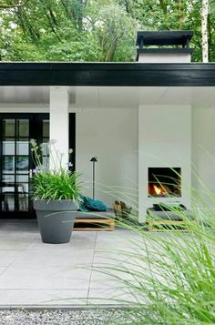 Clean, contemporary backyard. Gravel, white, patio fireplace, plants | Stijlvol wonen magazine