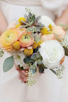 Arrangement of ranunculuses, garden roses, craspedia, succulents, and seeded eucalyptus