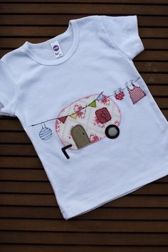 Hübsches und aufwändig gestaltetes Sommershirt mit einem niedlichen Wohnwagen, Wimpelkette, Lampion und kleiner Wäscheleine. Das Shirt ist aus rei...