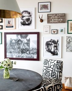 Gallery wall in dining space with black-and-white chair, modern light fixture, and white flowers