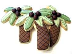 Palm tree cookies with 3D coconuts.  For the coconuts, she rolled the equivalent of a tootsie roll into a ball, rolled them on a texture mat and then cut them in half.