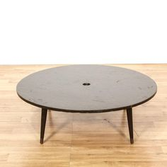 This mid century modern coffee table is featured in a solid wood with a distressed dark wood finish. This coffee table has a large round table top, a low base and tapered legs with worn brass feet. Perfect for serving drinks and snacks in a living room! #americantraditional #tables #coffeetable #sandiegovintage #vintagefurniture
