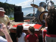 Clair Rankin cut the Canada Day Cake at the band stand as folks lined ...