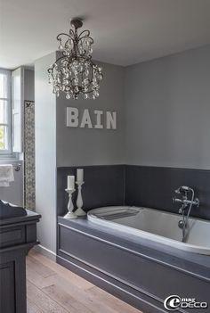 Dans une salle de bains, suspension 'Côté Table' et bougeoirs 'Ikea', lettres chez 'Cultura', habillage de baignoire en bois peint