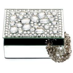 "This stunning Victoria jewelry box. The top of the box is lavishly encrusted with large sparkly crystals, while the sides are covered with shimmering Silver mirror. The jewelry box has two compartments lined in dramatic Black velvet. The jewelry box measures 5"" wide by 4"" deep by 2.5"" tall.  Match it with the Victoria Frame."