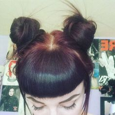 Double buns hairstyle with bettie bangs on burgundy hair