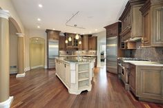 Large newly constructed luxury home with rambling kitchen room with floor-to-ceiling custom brown cabinetry and large white island.