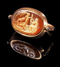 Cameo of agate with transparent brown and ivory layer. Two satyrs and Eros sitting in a grove, wrapping thyrsus with a ribbon. Wonderful and charming task. Probably Italy, 17th century A.D.
