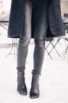 Grey jeans, black boots, charcoal coat for a casual, textured winter look