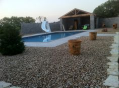 GroundScape, a Fort Worth Landscape Company, installs a zeroscape landscape around a pool.  A zeroscape is a landscape that requires no water.  The Pool house in the background was also built by GroundScape.