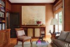 The den, wrapped in a jute wall covering by Stark, features a large Twombly, a Regency side cabinet and slipper chair, and a Michaelian & Kohlberg rug