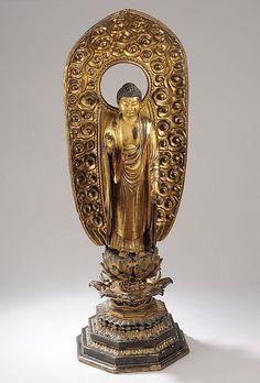 Buddha Amida debout sur le lotus les mains dans le geste de l'enseignement et de l'apaisement vêtu d'une longue robe monastique et auérolé d'une mandorle orné de nuages bouillonnnants . Bois laqué et doré. Japon. Période Edo