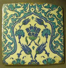 Tile two of two. Forming part of panel,with stylised carnations in cartouches of other flowers in lobed arches. Made of cobalt painted and cobalt, turquoise-green stained pottery.