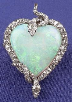 Edwardian Platinum, Opal, and Diamond Snake Pendant/Brooch, designed as a heart-shaped opal entwined by two old mine and old European-cut diamond serpents..: