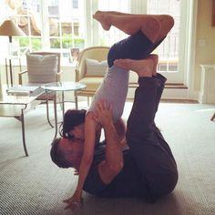 Hilaria and Alec Baldwin striking a couple's yoga pose