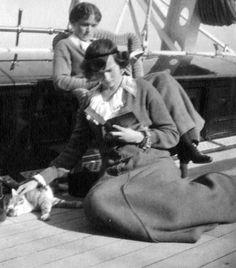Grand Duchesses Olga and Tatiana (stroking cat) reading on the Standart, c. 1914.
