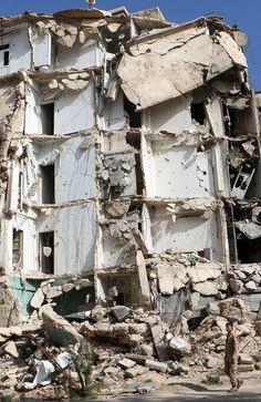 Devastation ... A man walks past a building after a barrel bomb attack.