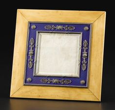 A Picture Frame by Faberge, St. Petersburg, workmaster Karl Armfelt. With blue enamel over engine turned ground, with banded reed inner border and beaded outer border, with silver palmette and roundel pendants and roundels at corners, within birch easel back frame.