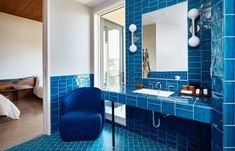 "Bathrooms tiled in blue, red, yellow or green inform the colour of each room's more subtle design elements, such as various Christian Rathbone throw pillows adorned in what Hills describes as ""hippie textiles,"" and custom bedside lighting by David Weeks. Austin Hotels, Bedside Lighting, Studio Room, Soft Seating, Hotel S, Lounge Areas, Bar Chairs, Small Living, White Walls"