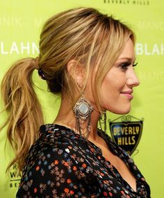 Hilary Duff sporting a mid length ponytail with bang-like hair on both sides