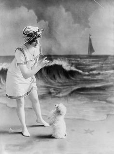 Young woman in bathing suit with small dog in front of studio backdrop of beach c. 1913.