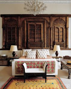An 18th-century Moghul façade from a merchant's  house is used as a headboard for a bed in the master bedroom of an London apartment. The European chandelier once hung in an Indian palace, the printed cottons on the pillows are from India, and the embroidered suzani is 19th century.       Photographer:     Simon Upton      Designer:     Matthew Patrick Smyth