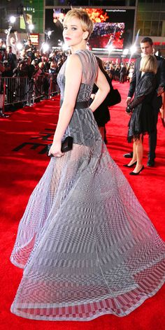 11/19/13: At The Hunger Games: Catching Fire premiere, Jennifer Lawrence dropped jaws in a belted sheer two-tone gray knitted Christian Dior Couture gown that she styled with Anita Ko jewelry and a black Roger Vivier box clutch. #lookoftheday