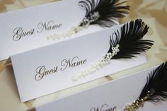 Wedding place cards Black & White feather and glass beads / rhinestones. €4,00, via Etsy.