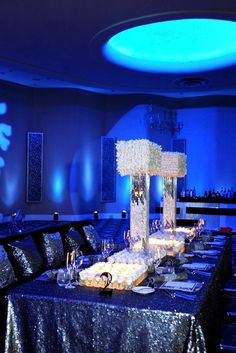 Gorgeous square shaped centerpieces and the sequined table linens and pillows on the sofa seating.