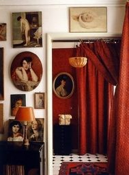Old portraits in differently shaped frames + red velvet curtains