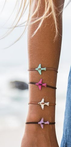 """You can't buy happiness - but you can buy a plane ticket - that's pretty close. Check out float's """"Airplane Colour"""" Bracelet from the classic Beachgold Collection. A tiny wooden airplane pendant carved from driftwood with a touch of colour."""