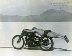 It is before 8 a.m. on the morning of Monday, September 13, 1948. Rollie Free lays stretched out on a stripped-down Vincent Black Shadow wearing nothing more than a swimsuit, a helmet and slip-on beach shoes as he streaks across the Bonneville Salt Flats in Utah. He is on his way to an astonishing 150 mph, and about to head into the record books. A photographer leans out of the window of a car tracking the Vincent and captures Rollie in one of the most iconic motorcycle images of all time.