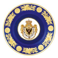 A PORCELAIN DESSERT PLATE FROM THE CORONATION SERVICE OF NICHOLAS I, IMPERIAL PORCELAIN MANUFACTORY, CIRCA 1826 painted royal blue, the cavetto with the Imperial Eagle and the chain of the Imperial Order of St. Andrew, the border richly gilded with swans, anthemion and wreaths, unmarked diameter: 21cm., 8¼in