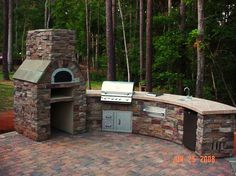 Exterior, Exciting Round Outdoor Kitchen With Chrome Patio BBQ Grill And Rustic Stones Outdoor Pizza Oven Also Concrete Top With Single Wash...