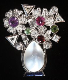 PLATINUM, DIAMONDS AND GEMSET GIARDINETTO BROOCH, LAST HALF 20TH CENTURY. In floral form, modeled as an oval moonstone shaped vase, set with 21 diamonds of trillion, round, brilliant and baguette shape with other gemstone flower heads, in a platinum setting.