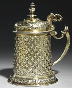 CHOPE EN VERMEIL. A GERMAN SILVER-GILT TANKARD MAKER'S MARK OF HANS UTTEN, NUREMBERG, CIRCA 1609 The spreading foot with ovolo border, the body and cover with hob-nail ornament divided by matting, the handle with beaded border terminating in a putto's mask, the double scroll thumbpiece with central caryatid, the cover with baluster finial. COLLECTION YVES SAINT LAURENT ET PIERRE BERGÉ.
