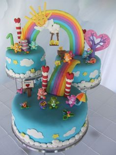 Care Bear Cake - This is a Care Bear theme cake that I made for my niece's 1st birthday. It is 3 seperate cakes all covered in fondant with gumpaste decorations. The only thing non edible are the little Care Bears my sister purchased. All three are vanilla cake with vanilla custard filling. This cake was a lot of fun to make. The colors are nice and bright. It was time consuming to make every little detail but definetely worth the work. Hope you all enjoy it. Thanks for looking.