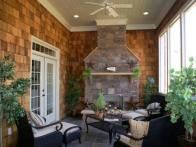 A screened porch's traditional  stacked stone fireplace  is set against shingled walls, mixing textures in an eye-catching way.