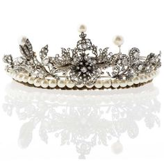 Gold, silver and diamond tiara, set with cultured pearls, 2 large baroque pearls, rose cut diamonds and 120 old brilliant cut diamonds weighing approx. 7 ct., the largest diamond weighing approx. 0.7 ct, a centre flower set en tremblent, some synthetic diamonds were replaced by spinel and zircon, late 19th early 20th century