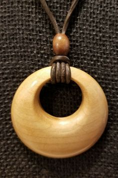 "2 1/4"" diameter hard maple pendant on adjustable brown leather necklace. By the Woodchuck of Woodburn."