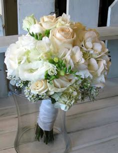 Lush combination of cream roses, white lisianthus, white hydrangea, white freesia, wax flower in a large formal bouquet, stem wrapped in cream ribbon and faux pearl studs.