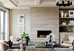 By Terrat Elms, this living room has coffered ceilings and an electric fireplace with a modern stone surround.