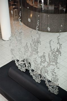 Concrete Lace, designed by Doreen Westphal, is made from ultra high performance concrete (fabricated by G.tecz) and different suspension materials like ribbon or 1mm steal cable. During the making process the suspensions are casted inside the lace-shaped concrete tiles.