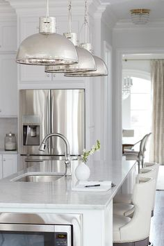 A honed carrera marble island, fitted with a stainless steel sink and satin nickel faucet, is lined with three off-white upholstered counter stools illuminated by three hammered nickel light pendants.