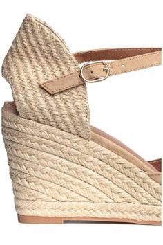 Sandali con zeppa e plateau rivestiti in iuta intrecciata. Cinturino regolabile alla caviglia con fibbia in metallo. Soletta in finta pelle. Suola in gomma.