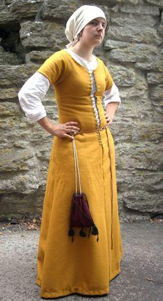 Denna gyllengula klänning är inspirerad av av de mellanklänningar som kvinnor av enklare börd från slutet av 1400-talet avporträtterats i. Den är handsydd med lintråd och ullgarn i ett underbart ylletyg (som tyvärr sticks...) Till klänningen hör särken i blekt linnetyg samt huvudduken i samma tyg. Den har fyra nedsydda veck som tyvärr inte syns så bra på denna bild. Från bältet hänger en påse av ylletyg fodrad med linnetyg, prydd med några söta tofsar. Jag är på jakt efter ett bättre bälte…