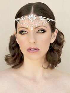 This dramatic and glamorous silver rhinestone bridal forehead hair piece is for the exotic bride or the bride who really wants to make a statement. Stunning!  Pieces is a very slight light gold and is attached to a black elastic headband so that it slips easily around your forehead.