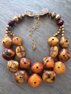 by Anna Holland | Necklace; faux amber beads which originated in Germany, but were traded and found most often in Mauritania and Niger. They are approximately 100 years old, very rare and highly collectible. They have been combined with old Tuareg and Ethiopian brass bicone beads, and a bronze hook and eye clasp | Sold