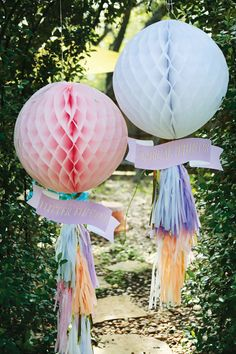 Woodsy & Magical Butterfly Birthday Party:– Giant honeycomb balls with pastel tissue tassel garlands fluttering in the wind